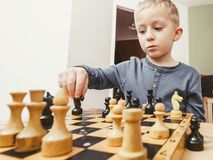 下棋的小孩男孩获得乐趣 免版税图库摄影