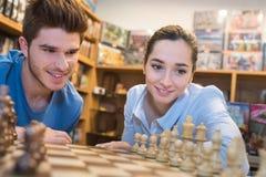 下棋的愉快的夫妇在比赛商店 免版税库存照片