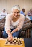下棋的确信的资深妇女画象在桌上 免版税图库摄影