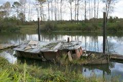 下沉的被放弃的红色小船一半 免版税库存图片