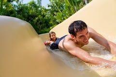 下滑下来水滑道的父亲和女儿。 免版税图库摄影