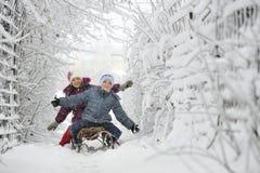 下滑在冬时的孩子 免版税库存照片