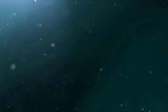 从水下的背景的抽象深蓝色海浪与微微粒拂去流动的灰尘,光线发光 免版税图库摄影