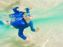 水下的年轻男孩乐趣在有风镜的海 暑假乐趣 库存照片