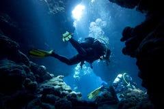 水下的洞的轻潜水员 库存图片