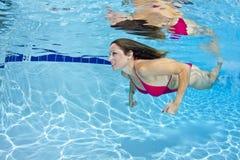 水下红色的比基尼泳装的妇女 免版税库存图片