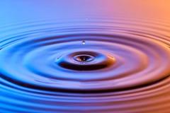 水下落关闭与同心波纹五颜六色的蓝色和a 库存照片
