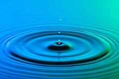 水下落关闭与同心波纹五颜六色的蓝色和g 免版税图库摄影