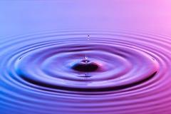 水下落关闭与同心波纹五颜六色的蓝色和p 库存图片