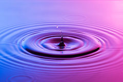 水下落关闭与同心波纹五颜六色的蓝色和p 免版税库存照片