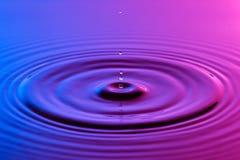 水下落关闭与同心波纹五颜六色的蓝色和p 免版税库存图片