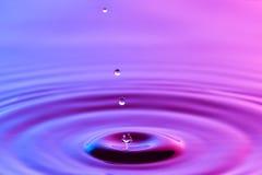 水下落关闭与同心波纹五颜六色的蓝色和p 图库摄影
