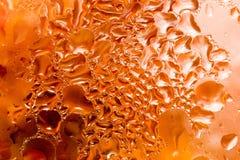 下落抽象背景在一块红色玻璃的 库存图片