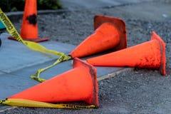 下落的橙色交通锥体和小心磁带 免版税库存图片