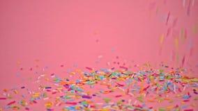 下跌在桃红色背景、装饰的蛋糕和面包店,慢动作的Sprinkles 股票视频