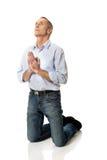 下跪和祈祷对上帝的人 库存照片