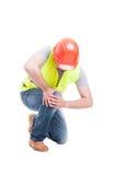 下跪和遭受膝盖痛苦的男性建设者 图库摄影
