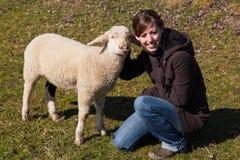 下跪在一只小羊羔旁边的妇女 库存照片