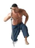 下跪在地板上的肌肉人赤裸上身,与日本剑 图库摄影