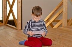 下跪在地板读书的小男孩 免版税库存照片