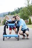 下跪在步行者的残疾儿子旁边的父亲 免版税库存图片