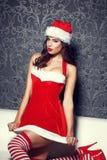下跪在沙发的性感的圣诞老人妇女 库存图片