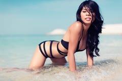 下跪在海滩的女孩在水中 免版税库存图片