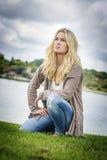 下跪在湖的白肤金发的妇女 免版税库存图片