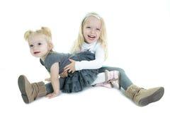 下跪在的两个逗人喜爱的矮小的白肤金发的姐妹 免版税图库摄影