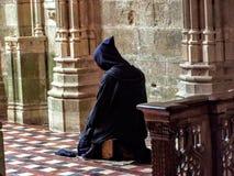 下跪在谦逊的祷告的宽容基督徒修士请求上帝帮忙 库存照片