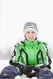 下跪在雪的年轻男孩做雪球 免版税图库摄影