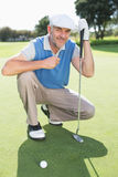 下跪在高尔夫球区的微笑的高尔夫球运动员 库存照片