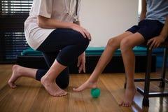 下跪由男孩的女性治疗师的低部分跨步在重音球 库存照片