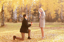 下跪的人提出圆环对一名妇女在秋天 库存照片
