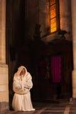 下跪的修士在黑暗的教会里 库存图片