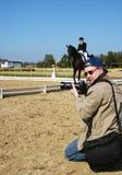 下跪的摄影师被转动的头,射击室外骑马驯马英国骑马体育竞赛,马的女骑士Jokey 库存照片