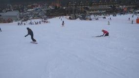 下降在新鲜的雪的挡雪板在冬天依靠 滑下来在山的多雪的倾斜的无法认出的人 股票录像