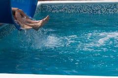 下降在水池的一张幻灯片的游人的腿 库存图片