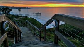 下降对海滩的楼梯在日落 库存照片