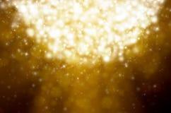 下降的雪花和的星,金黄光 免版税库存图片
