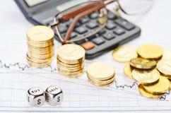 下降趋势堆积硬币,计算器,玻璃并且把立方体切成小方块 免版税库存图片