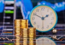 下降趋势堆金黄硬币、时钟和财政图 免版税库存图片