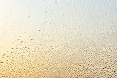 下雨下落和冻水在玻璃窗背景 免版税图库摄影