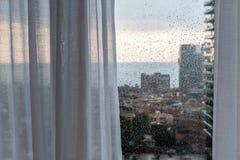 下雨在一个窗口的下落有现代城市视图 库存图片