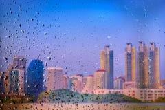 下雨在一个玻璃窗的下落有被弄脏的城市背景 库存图片