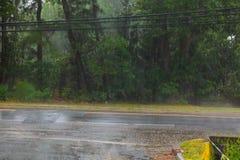下雨在水、雨在沥青或创造波纹的柏油碎石地面路的下落, 库存照片