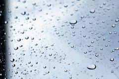 下雨在汽车清楚的玻璃风屏幕上的下落,雨小滴 库存照片