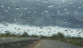 下雨在汽车玻璃的下落 免版税库存图片