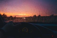 下雨在汽车玻璃背景的下落与红色日落 库存图片