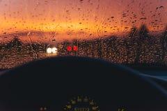 下雨在汽车玻璃背景的下落与红色日落 库存照片